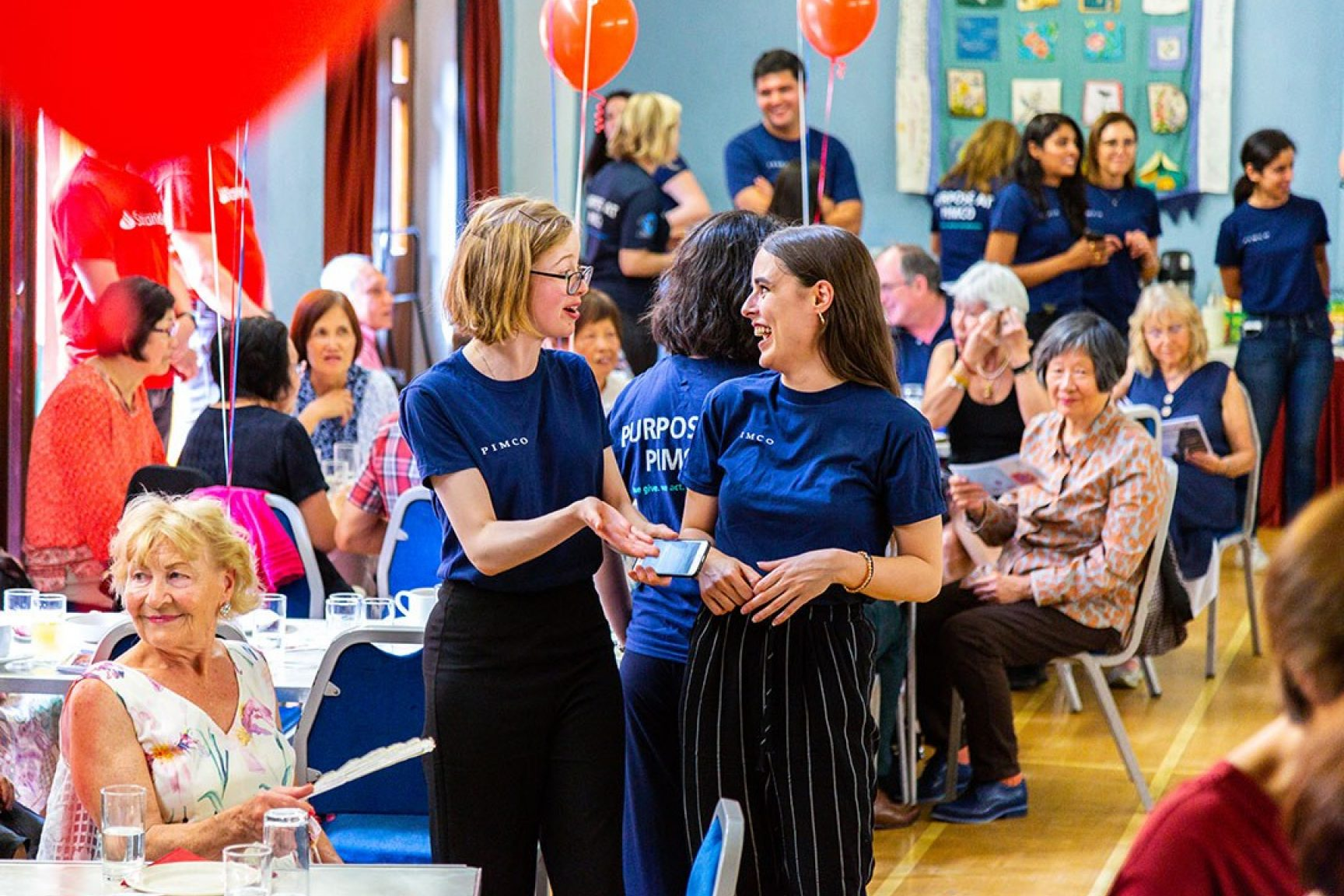 A community event, there are balloons, people seated at tables having a nice time. There a two volunteers chatting and smiling at each other in the middle of the photo.