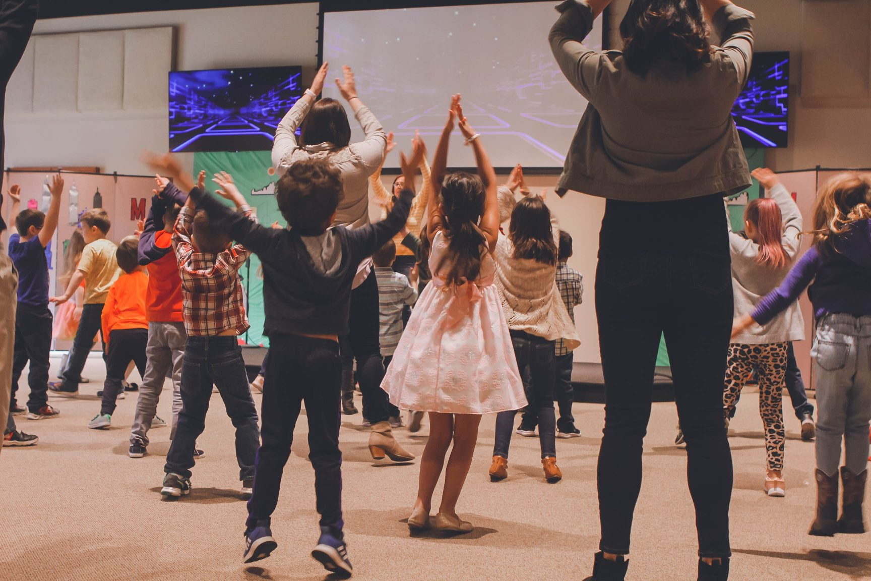Children with their hands in the air taking part in a group activity.