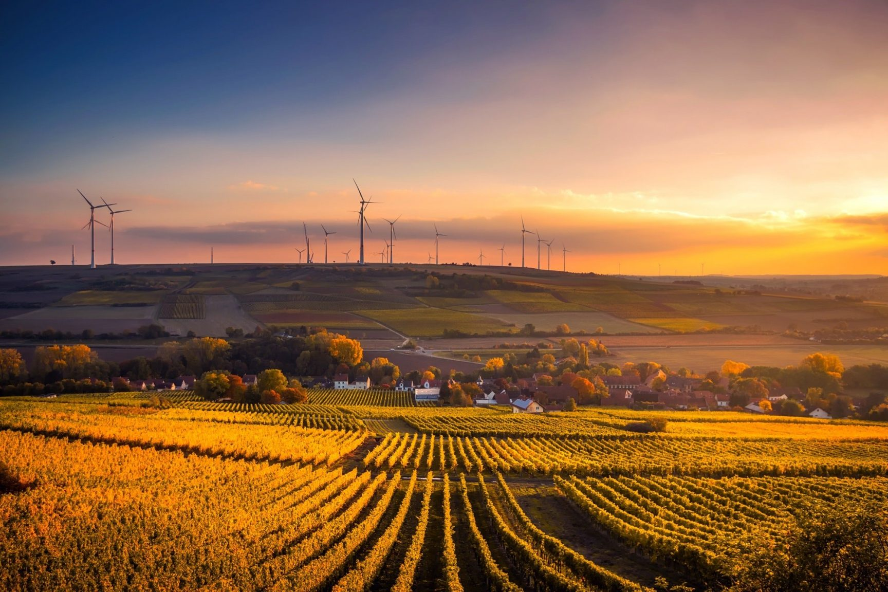 A landscape at sunset. There is a field of crops, a small valley with a village, and wind turbines in the distance.