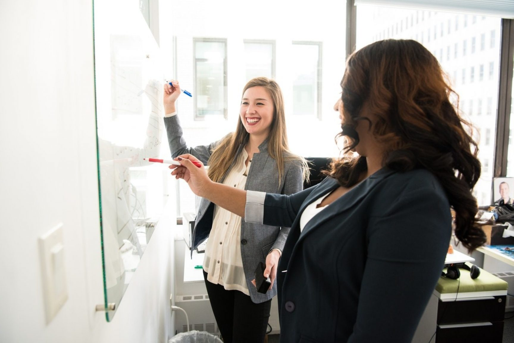 Two women at work. They are working together at a whiteboard. They are smiling.