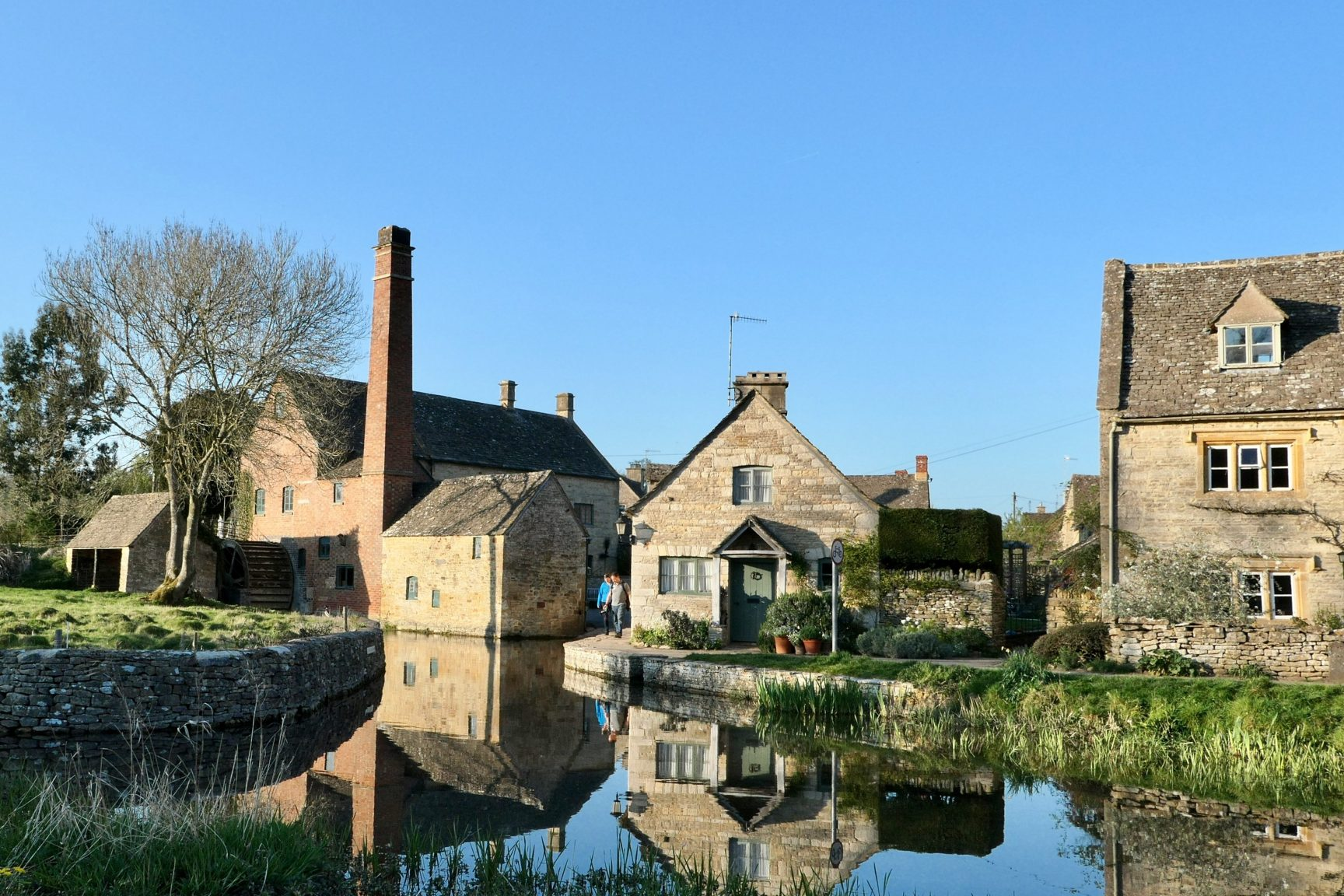 Small cottages beside a small stream with a water mill. It's a lovely sunny day and the village looks quaint.